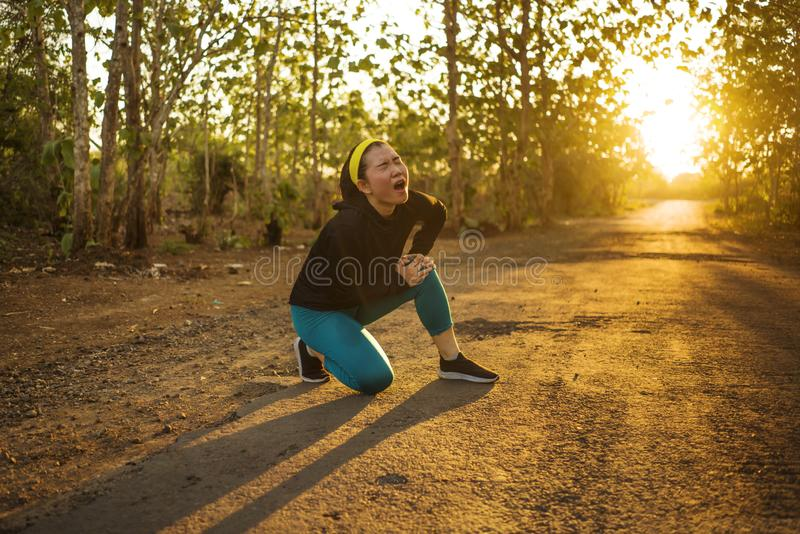 Fitness lifestyle portrait of young attractive Asian runner woman suffering sport injury during jogging workout on sunset road stock image