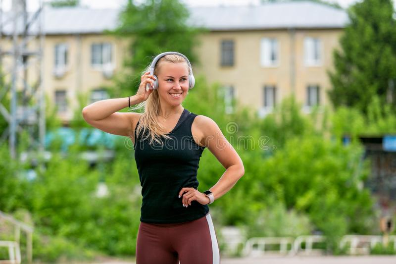 Fitness lifestyle. Sports young woman posesin headp hones. Workout at the stadium. Healthy life concept. Horizontal photo stock photo