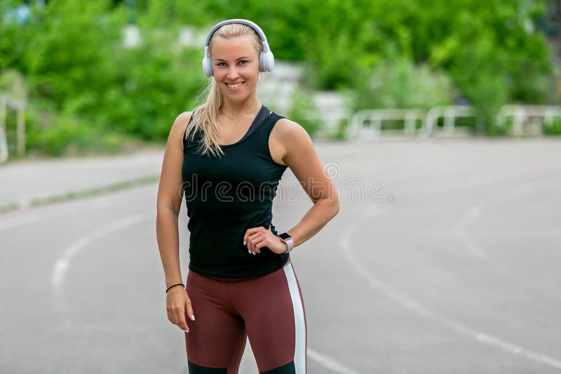 Fitness lifestyle. Sports young woman posesin headp hones. Workout at the stadium. Healthy life concept. Horizontal photo royalty free stock photography