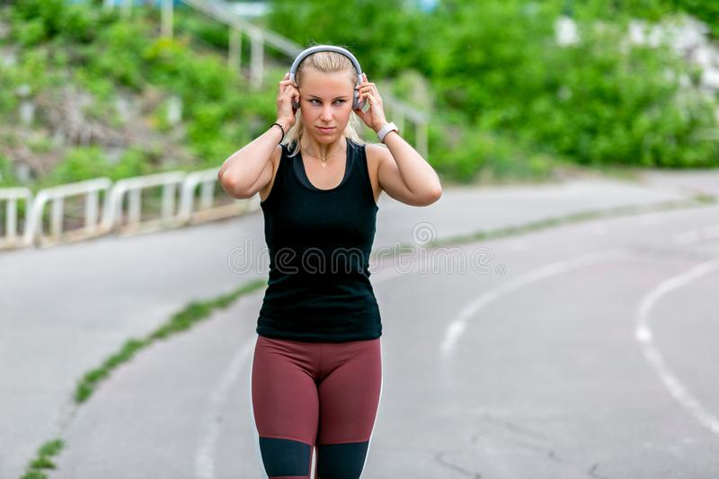 Fitness lifestyle. Thirty-year-old young woman runs in headphones. Workout at the stadium. Healthy life concept royalty free stock photo