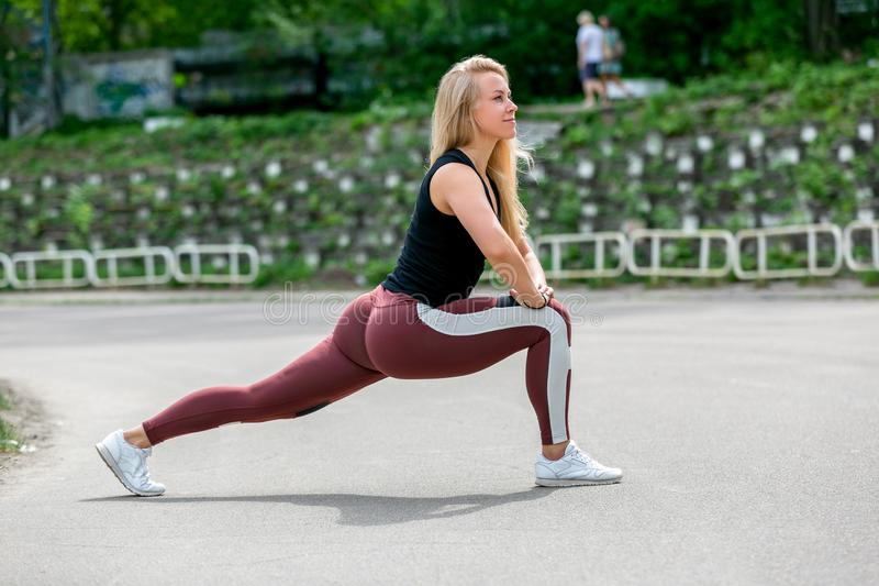 Fitness lifestyle. Young woman doing lunges to the side. Workout at the stadium. Healthy life concept. Horizontal photo.  royalty free stock images