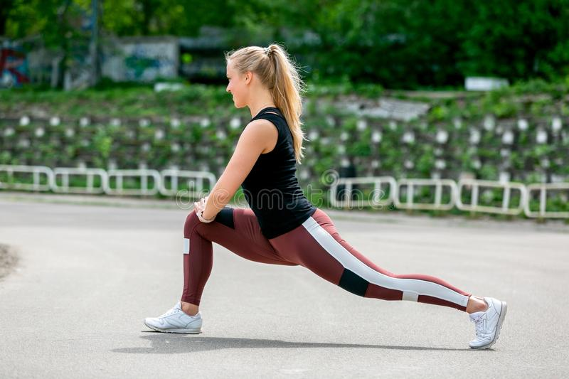 Fitness lifestyle. Young woman doing lunges to the side. Workout at the stadium. Healthy life concept. Horizontal photo.  royalty free stock photos