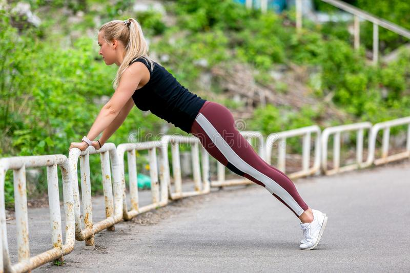 Fitness lifestyle. Young woman doing push ups in the slope. Sporty young blonde girl on a sunny day at the stadium. Healthy life. Concept. Horizontal photo stock images