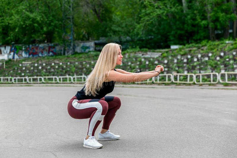 Fitness lifestyle. Young woman doing squats. Workout at the stadium. Healthy life concept. Horizontal photo.  stock images