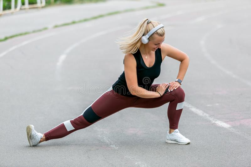 Fitness lifestyle. Young woman in headphones warming up before training doing exercises to stretch her muscles and joints. Workout stock photos