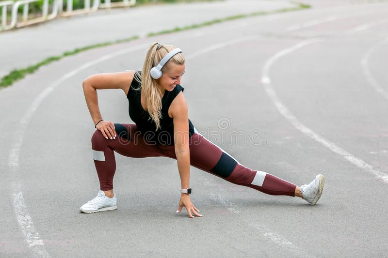 Fitness lifestyle. Young woman in headphones warming up before training doing exercises to stretch her muscles and joints. Workout royalty free stock images