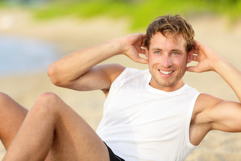 Fitness man doing crunches sit-ups on beach royalty free stock image