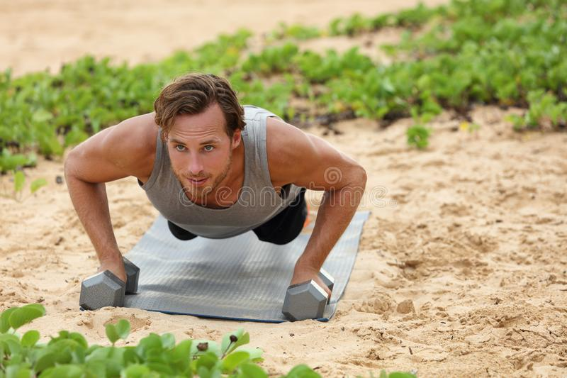 Fitness man doing plank push-ups exercise on dumbbell weights on beach. Bodyweight floor exercises healthy lifestyle stock images