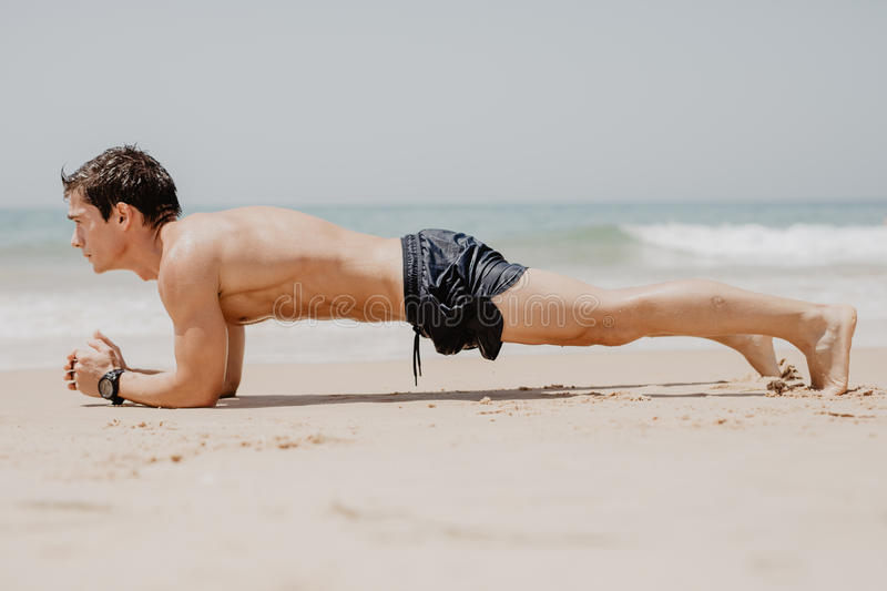 Fitness man doing push-up exercise on beach. Portrait of fit guy working out his arm muscles and body core with pushup exercises o stock photos