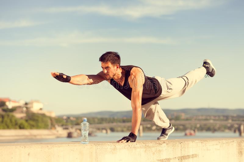 Fitness man doing push-ups on one arm and one leg. Outdoor workout and sport lifestyle concept royalty free stock photos