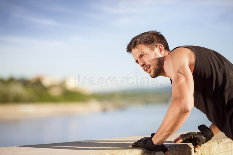 Fitness man doing push-ups on wall by river. Strong hand of muscular man while he is doing a push-ups stock image