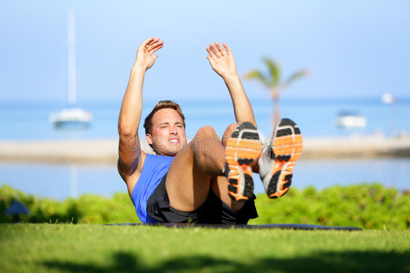 Fitness man doing sit-ups exercise for abs. Outdoors. Fit male athlete cross training jackknife sit up during workout. Muscular handsome young caucasian man stock image