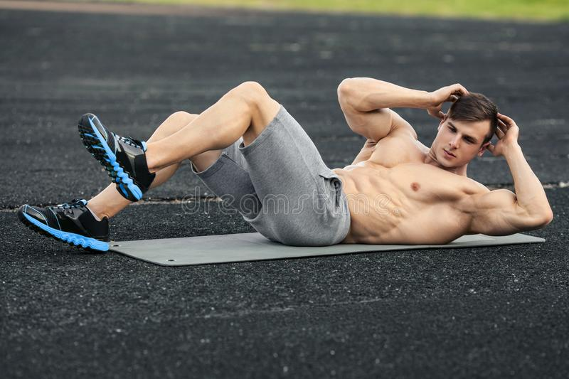 Fitness man doing sit ups in the stadium working out. Muscular male exercising abdominals, outdoor royalty free stock photo