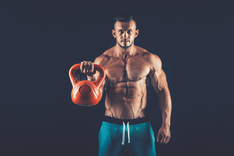 Fitness man doing a weight training by lifting heavy kettlebell stock images