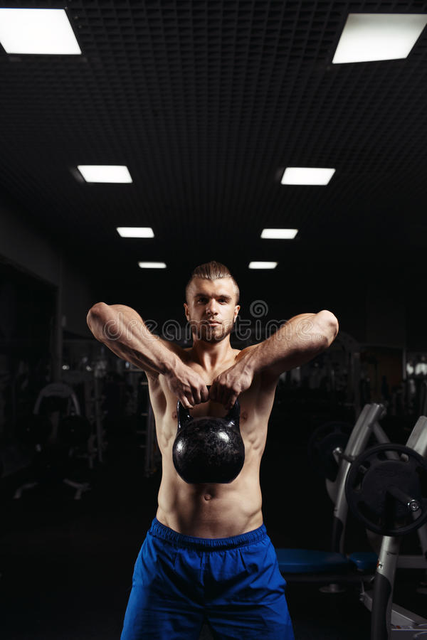 Fitness man doing a weight training by lifting heavy kettlebell royalty free stock photography