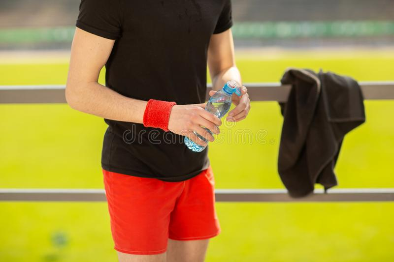 Fitness man drinking water from bottle. Thirsty athlete having cold refreshment drink after intense exercise stock photo