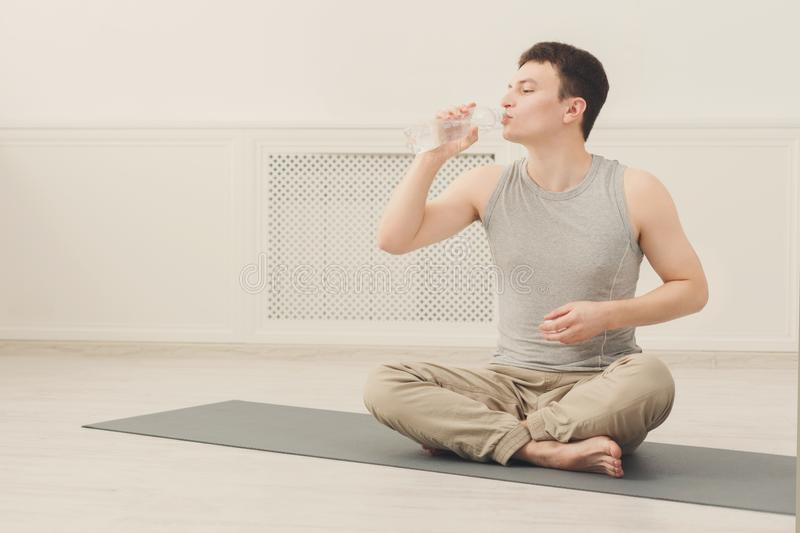 Fitness man drinking water at gym stock images