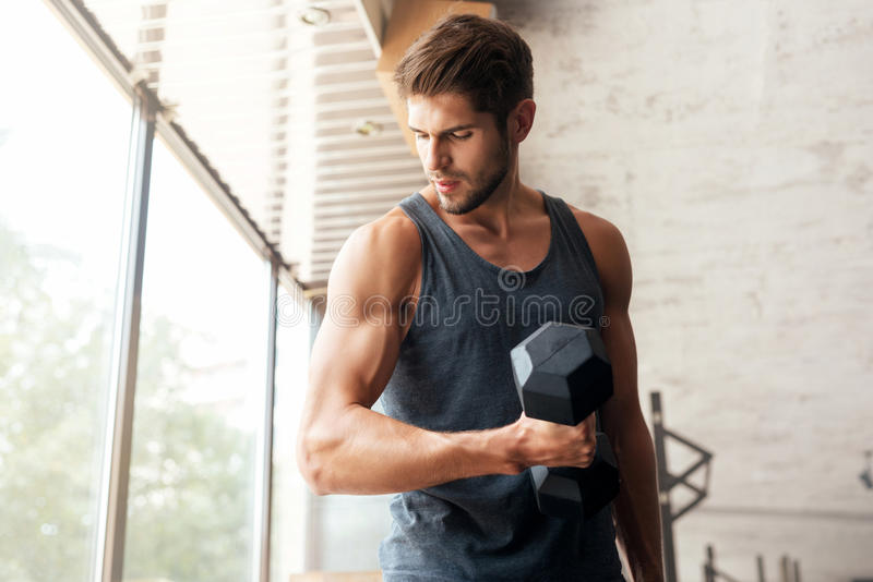 Fitness man with dumbbell in gym stock photo
