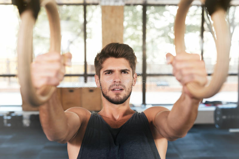 Fitness man is engaged on the rings stock photos
