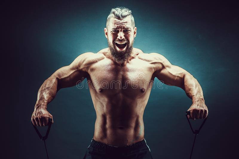 Fitness man exercising with stretching band. Muscular sports man exercising with elastic rubber band. Guy working out royalty free stock photography