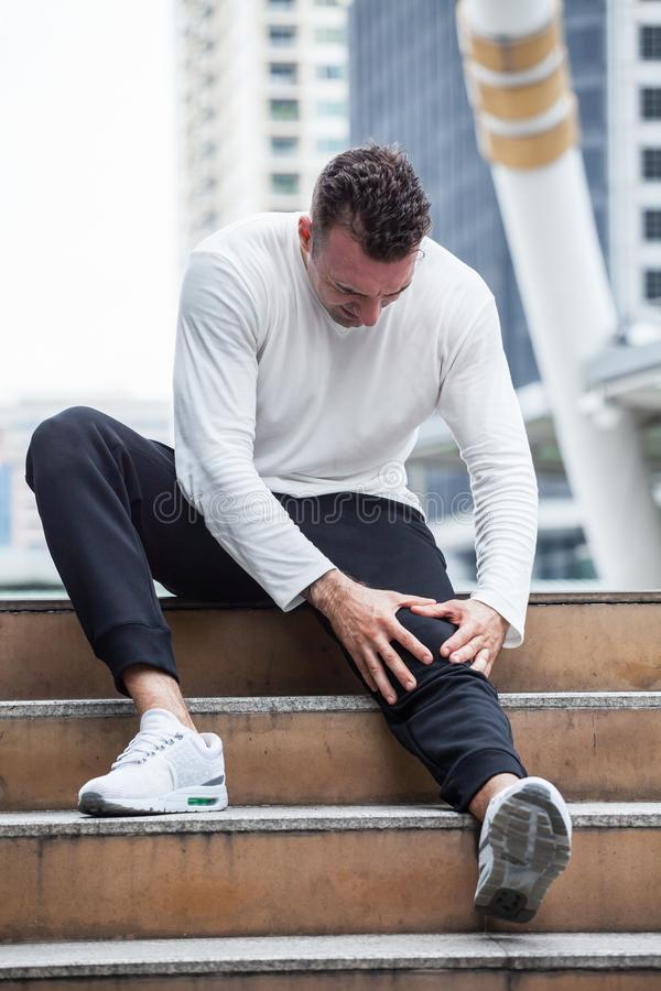 Fitness man have knee pain sitting on steps of stair in the city. sport injury leg of run in urban , accident , exercise,workout. Calf, thigh, ache, agony stock photography