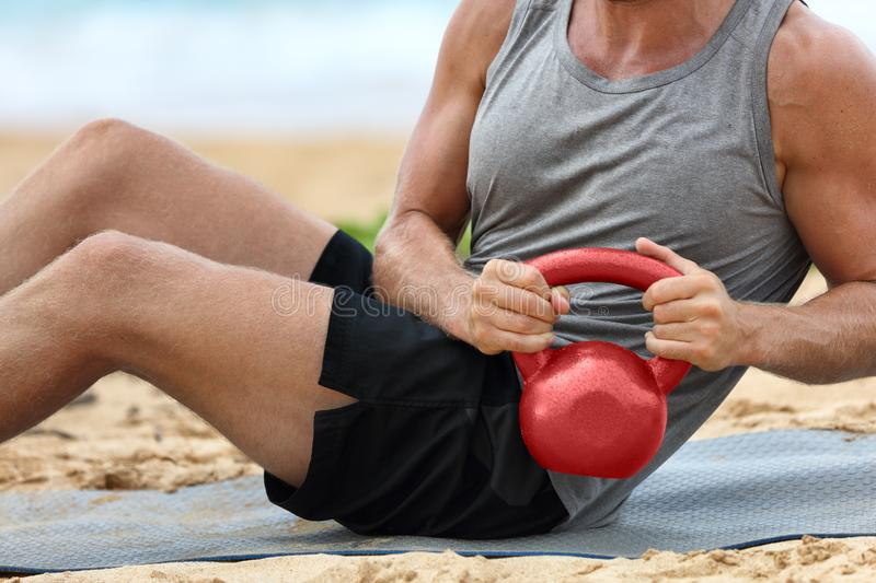 Fitness man lifting kettlebell weight training russian twist exercise. Exercising on beach training with kettlebells working out. Core, obliques and abdominal royalty free stock photo