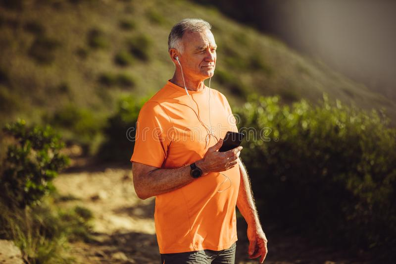 Fitness man listening to music and walking outdoors stock image