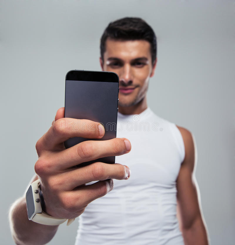 Fitness man making selfie photo on smartphone. Over gray background. Focus on smartphone stock photography
