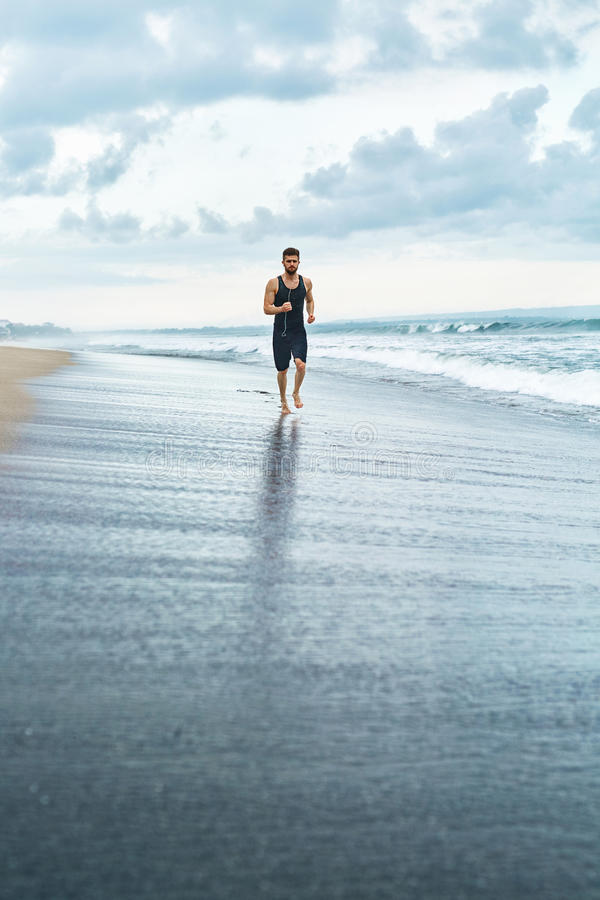 Fitness Man Running On Beach. Runner Jogging During Outdoor Workout royalty free stock image