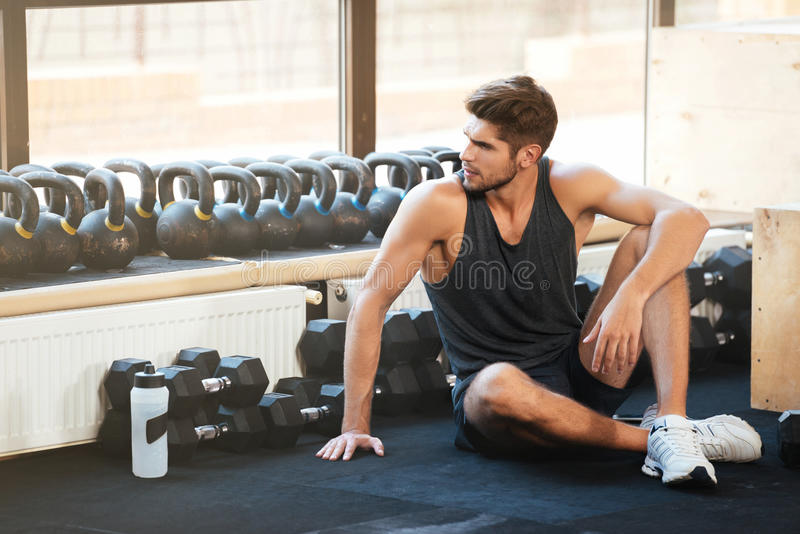 Fitness man sits on the floor stock image