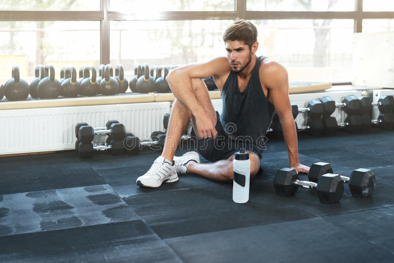 Fitness man sitting down in gym royalty free stock image