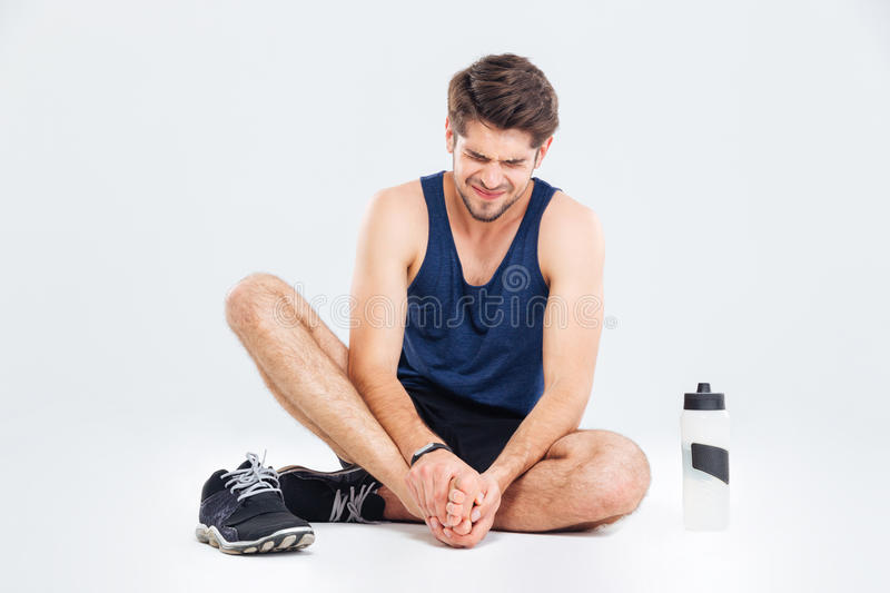 Fitness man sitting and suffering with foot pain. Over white background stock photo