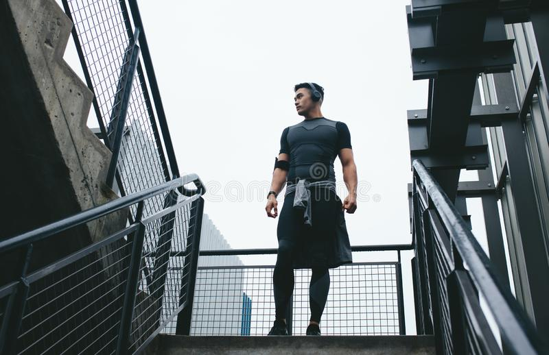 Fitness man standing on the steps outside. Low angle view of fitness man in sports wear standing on the steps outside. Fit man taking a break during workout stock photos