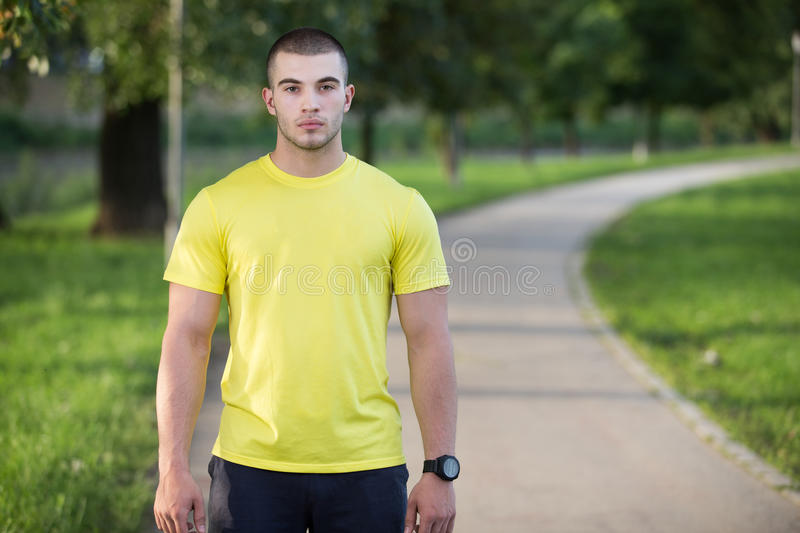 Fitness man stretching arm shoulder before outdoor workout. Sporty male athlete in an urban park warming up. royalty free stock images