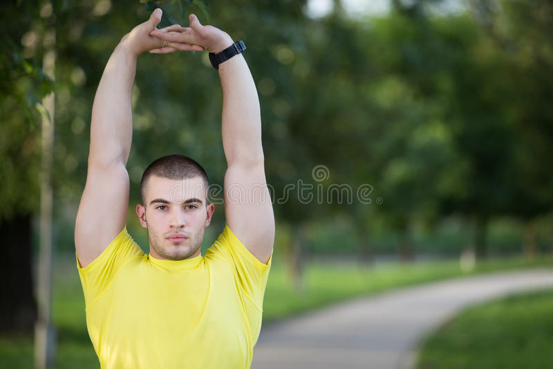Fitness man stretching arm shoulder before outdoor workout. Sporty male athlete in an urban park warming up. stock photos