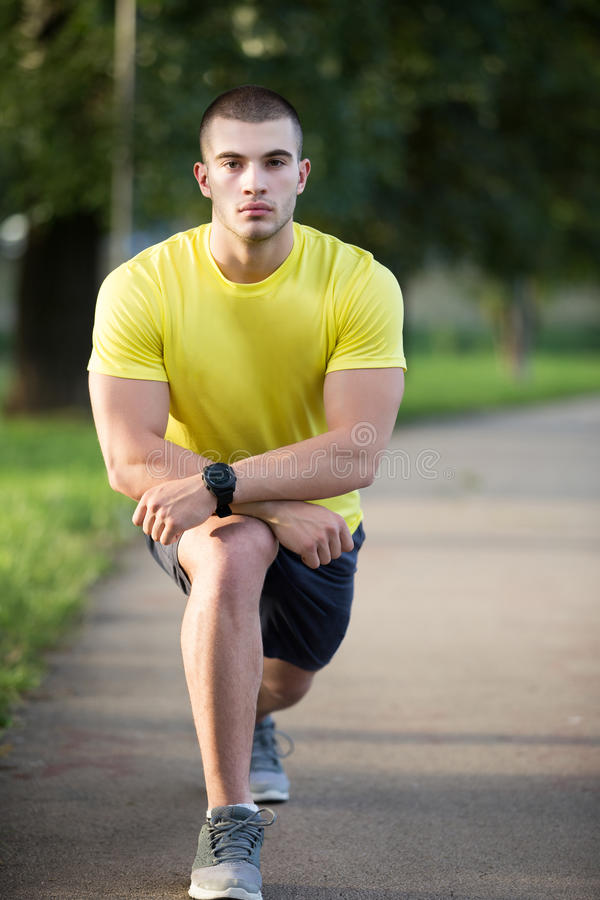 Fitness man stretching arm shoulder before outdoor workout. Sporty male athlete in an urban park warming up. royalty free stock photos
