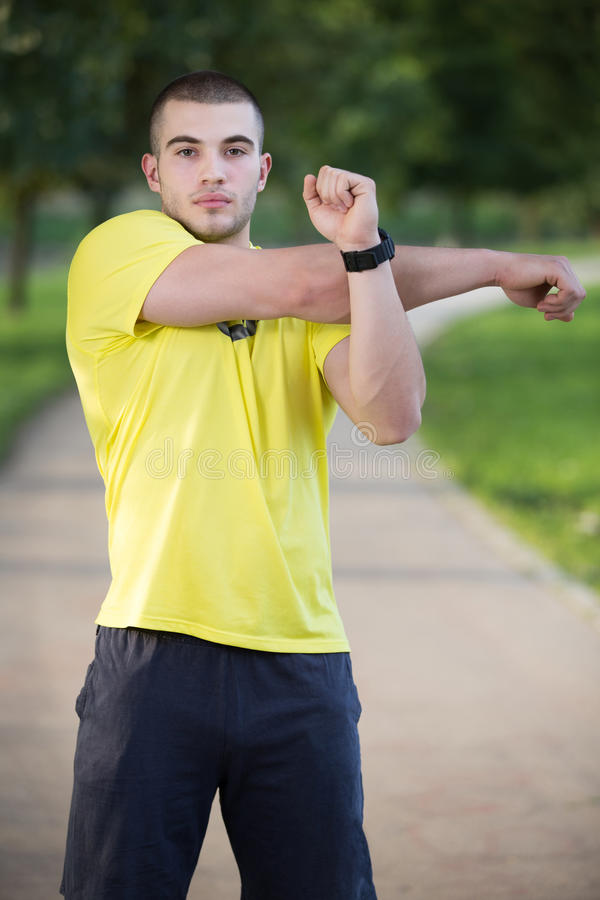 Fitness man stretching arm shoulder before outdoor workout. Sporty male athlete in an urban park warming up. royalty free stock photo