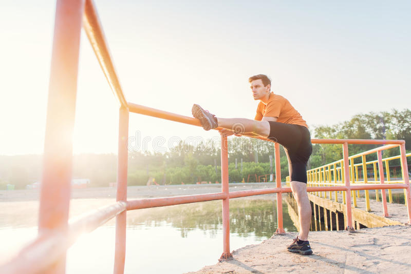 Fitness man stretching his leg muscles outdoors. stock image