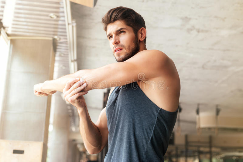 Fitness man warming up in gym stock photography