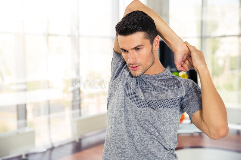 Fitness man warming-up at gym royalty free stock image