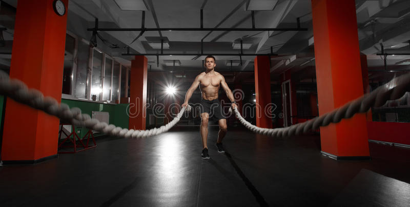 Fitness man working out with battle ropes at a gym stock images