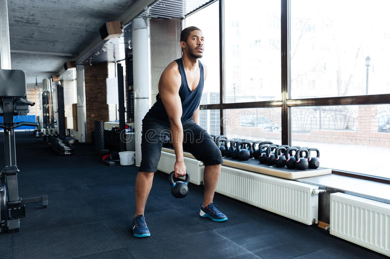 Fitness man working out with kettlebell stock photography