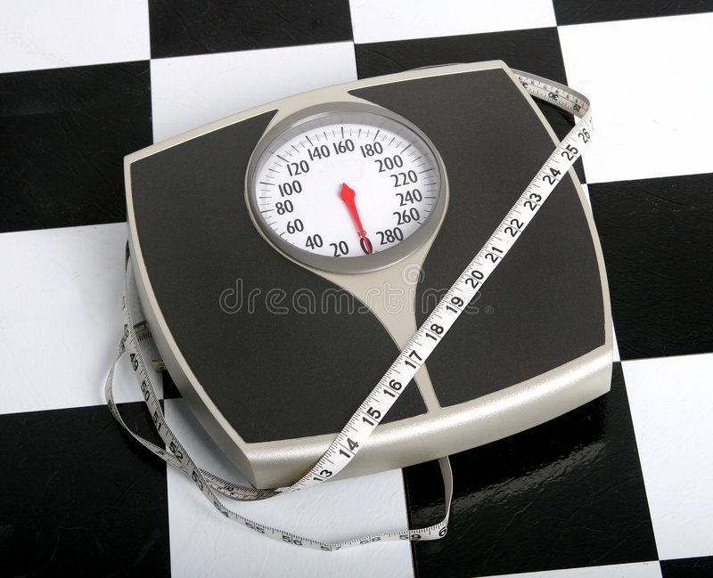 Fitness measures. Measuring tape atop scale on black and white tiled bathroom floor stock photography