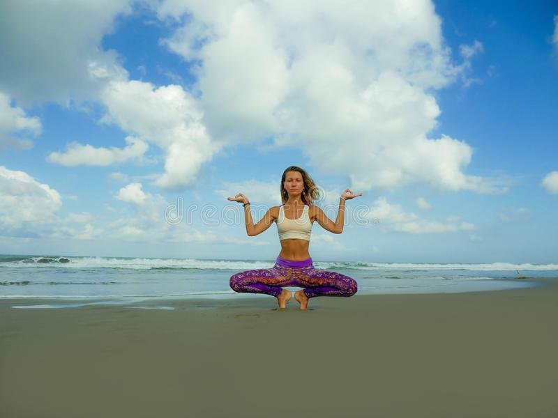 Young attractive and athletic woman in yoga lotus posture and at beautiful beach doing relaxation and meditation exercise under a stock photo