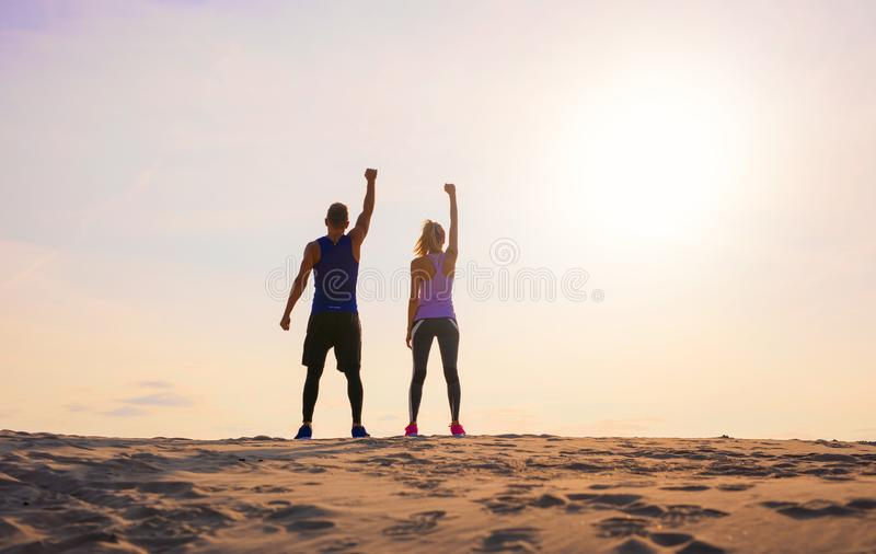 Fitness man and woman with arms up celebrating sport goals stock images