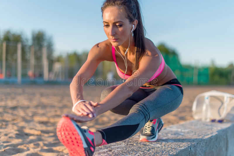 Fitness model athlete girl warm up stretching her hamstrings, leg and back. Young woman exercising with headphones royalty free stock image