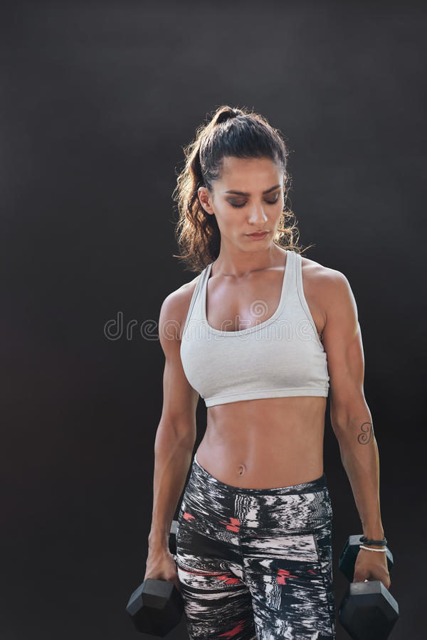 Fitness model exercising with dumbbells. Female fitness model exercising with dumbbells. Young female bodybuilder working out with hand weights on black royalty free stock photos