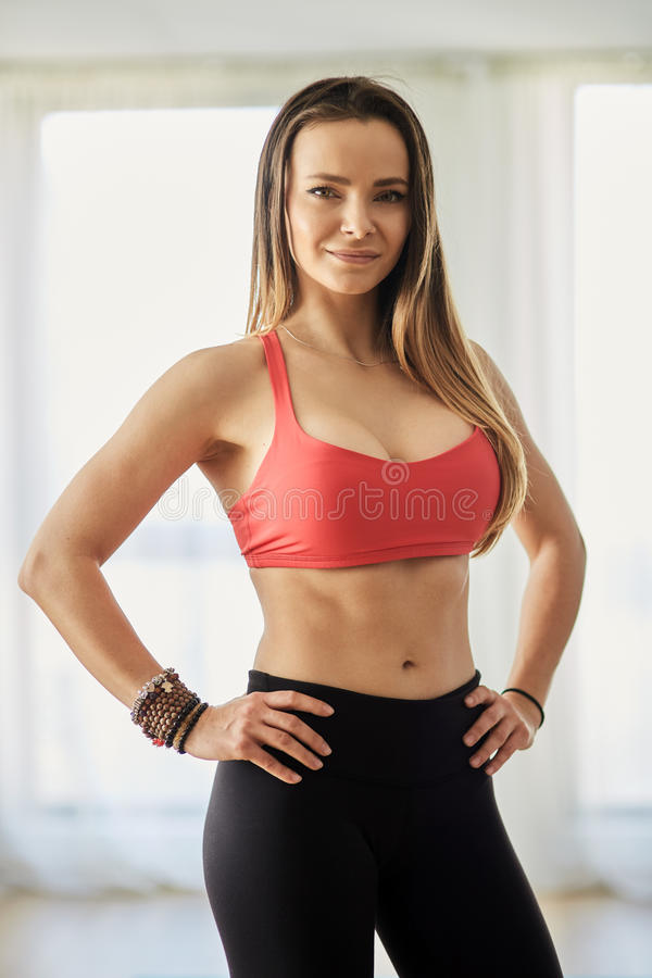 Fitness model indoor. Attractive fitness model in bra and yoga pants posing indoor royalty free stock photos