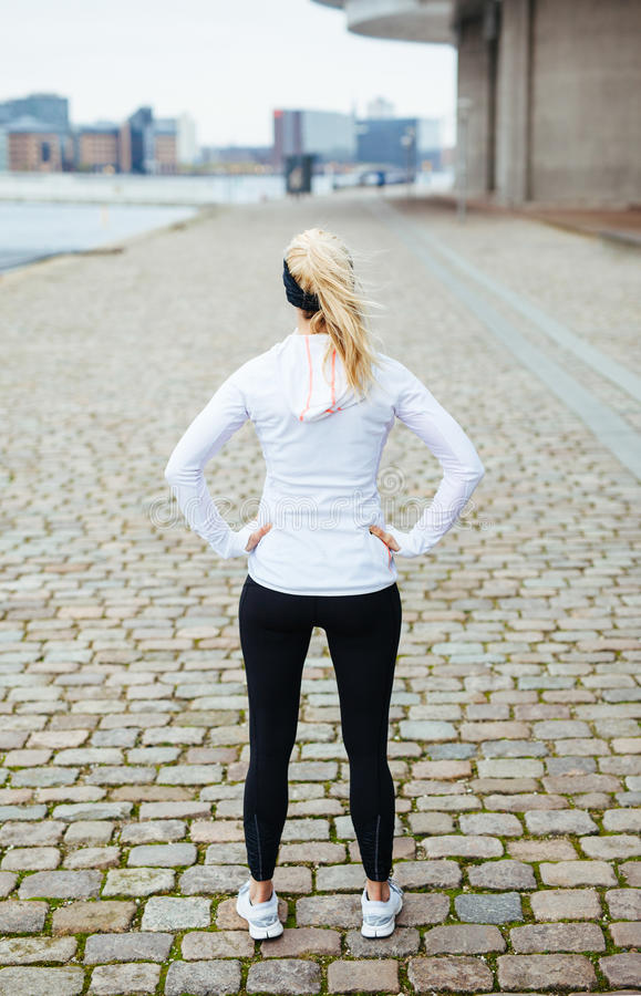 Fitness model looking forward for a city run. Rear view of young woman with her hands on hips standing on sidewalk. Fitness model looking forward for a city run royalty free stock photography
