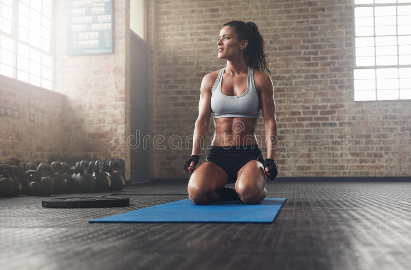 Fitness model in sportswear on exercise mat. Indoor shot of muscular young woman exercising at gym. Fitness model in sportswear sitting on exercise mat and royalty free stock photo